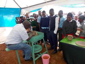 KU Staff demonstrating to High School students how to make a traditional pot
