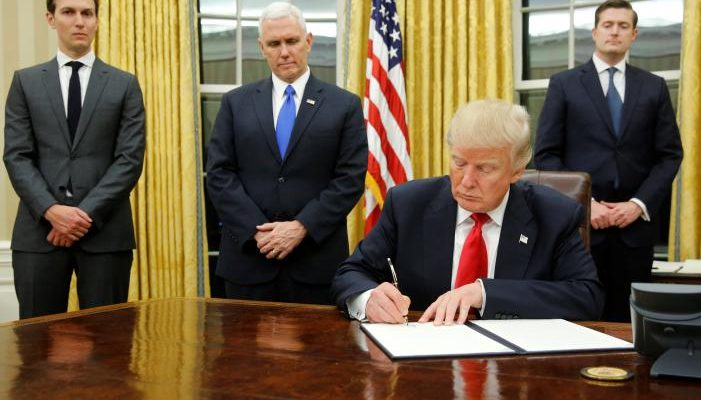 U.S. President Donald Trump, flanked by Senior Advisor Jared Kushner (standing, L-R), Vice President Mike Pence and Staff Secretary Rob Porter welcomes reporters into the Oval Office for him to sign his first executive orders at the White House in Washington, U.S. January 20, 2017. REUTERS/Jonathan Ernst